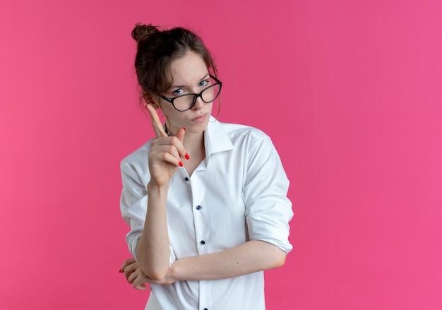 Jovem garota russa loira confiante com óculos mostra o dedo indicador isolado no espaço rosa com espaço de cópia