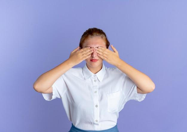 Jovem garota russa loira satisfeita fechando os olhos com as mãos