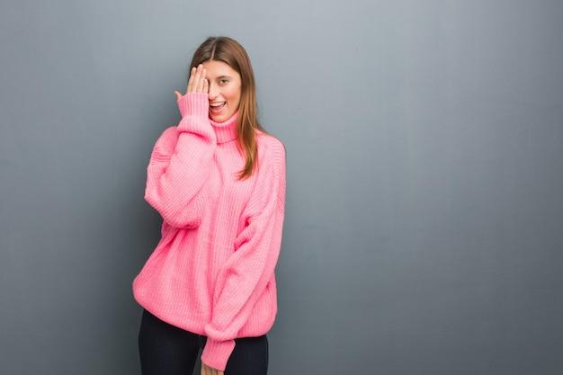 Jovem garota russa natural gritando feliz e cobrindo o rosto com a mão