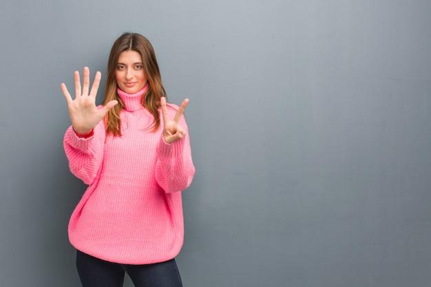 Jovem garota russa natural mostrando o número sete