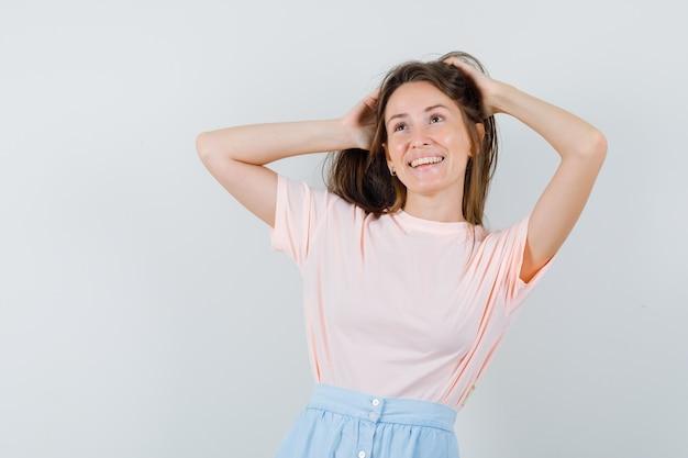 Jovem garota segurando as mãos no cabelo em t-shirt, saia e olhando alegre, vista frontal.