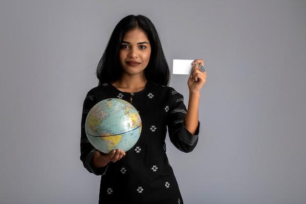 Jovem garota segurando o globo do mundo e posando com cartão de crédito em uma parede cinza.