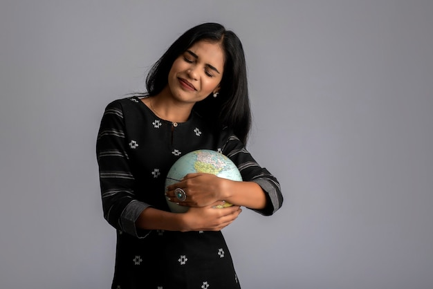 Jovem garota segurando o globo do mundo e posando em cinza.