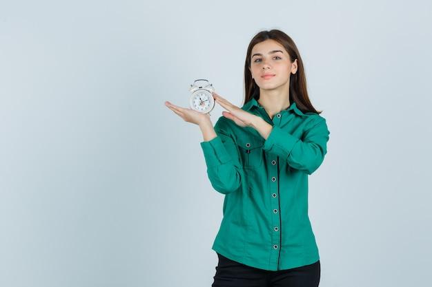 Jovem garota segurando o relógio com as duas mãos na blusa verde, calça preta e parecendo alegre. vista frontal.