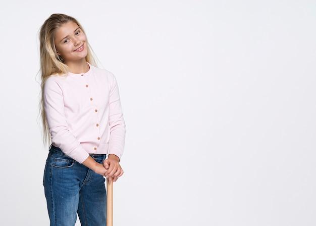 Jovem garota segurando o taco de beisebol com cópia-espaço