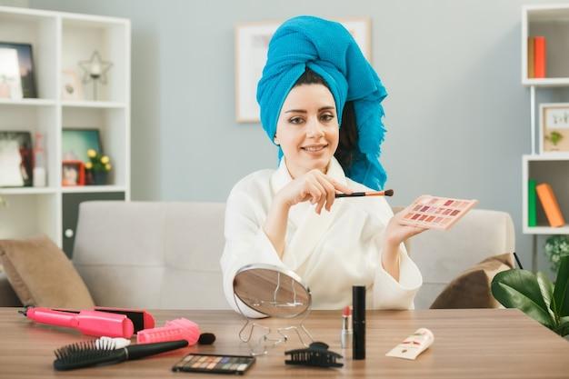 Jovem garota segurando paleta de sombra com pincel de maquiagem enrolado em uma toalha no cabelo, sentada à mesa com ferramentas de maquiagem na sala de estar