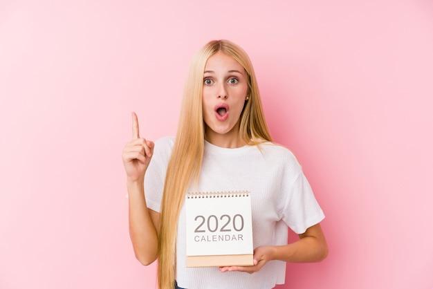 Jovem garota segurando um calendário de 2020, tendo uma ótima ideia, o conceito de criatividade.