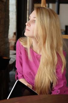 Jovem garota segurando um tablet digital, computador. mulher de negócios no café faz negócios. trabalhador de escritório na hora do almoço. mulheres em reunião no saguão do hotel.
