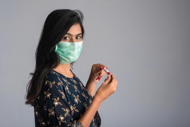Jovem garota segurando um tubo de ensaio com amostra de sangue para análise de coronavírus ou 2019-ncov.