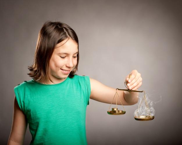 Jovem garota segurando uma balança da justiça com dinheiro e fumaça