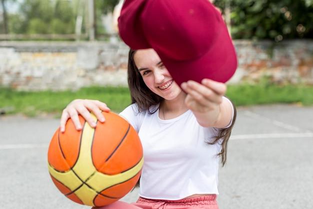 Jovem garota segurando uma bola de basquete e seu boné