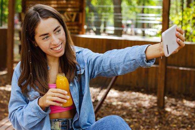 Jovem garota segurando uma garrafa de suco fresco e tirando uma selfie