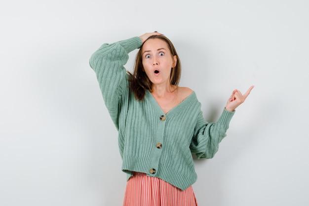 Jovem garota segurando uma mão na cabeça, apontando para a direita com o dedo indicador em malhas, saia e parecendo surpresa. vista frontal.