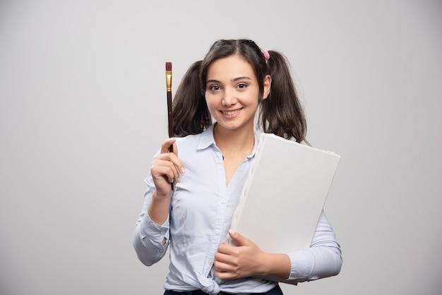 Jovem garota segurando uma tela vazia e pincel na parede cinza.