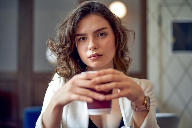 Jovem garota séria tomando café em um café