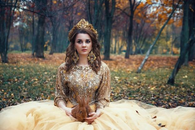 Jovem garota sexy bonita no vestido de ouro na floresta de outono
