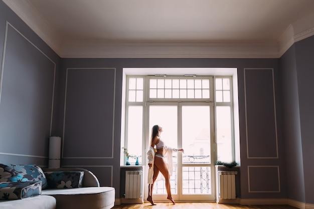 Jovem garota sexy com belas pernas em pé perto da janela