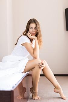 Jovem garota sexy em roupa íntima sentada na cama pela manhã