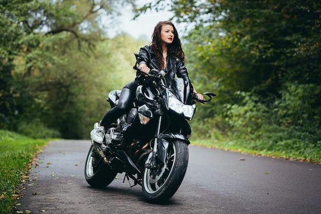 Jovem garota sexy em uma jaqueta de couro preta sentada em uma motocicleta esportiva preta em uma estrada na floresta