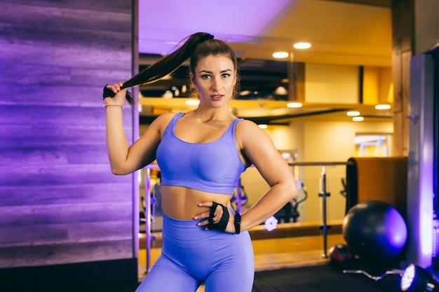 Jovem garota sexy fazendo um aquecimento na academia e posa com roupas azuis