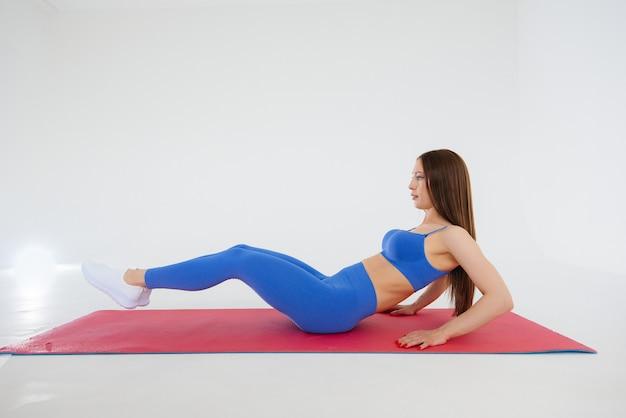 Jovem garota sexy realiza exercícios de esportes em um espaço em branco. fitness, estilo de vida saudável.