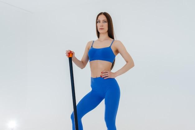 Jovem garota sexy realiza exercícios de esportes