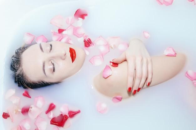 Jovem garota sexy tomando banho de leite com pétalas de rosa closeup