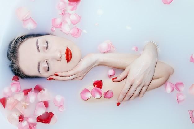 Jovem garota sexy tomando banho de leite com pétalas de rosa