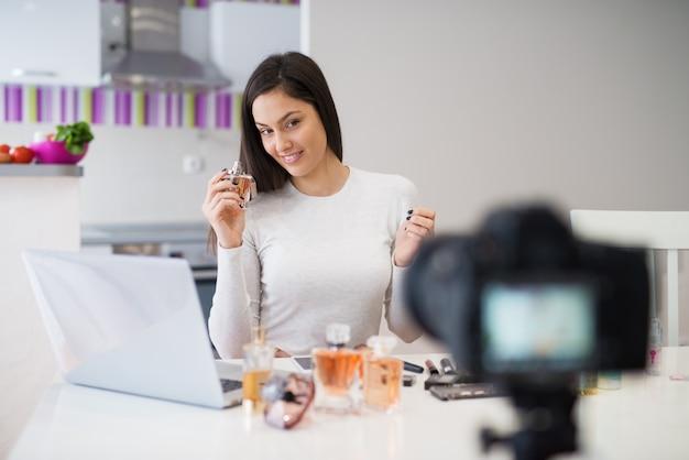 Jovem garota sorridente bonita está sentado na mesa da cozinha com um laptop e mostrando perfumes para a câmera.
