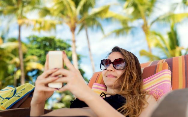 Jovem garota tomando uma selfie na praia. fazendo um verão quente tiro com palmeiras ao fundo.