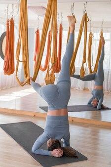 Jovem garota usa roupas esportivas para fazer ioga e alongamentos antigravitacionais na academia