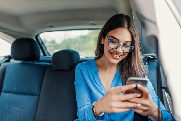 Jovem garota usa um telefone celular no carro. isolamento celular tecnologia