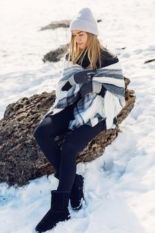 Jovem garota usando cobertor sentado na neve