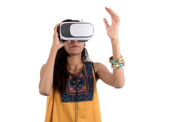 Jovem garota usando fone de ouvido de óculos de realidade virtual.