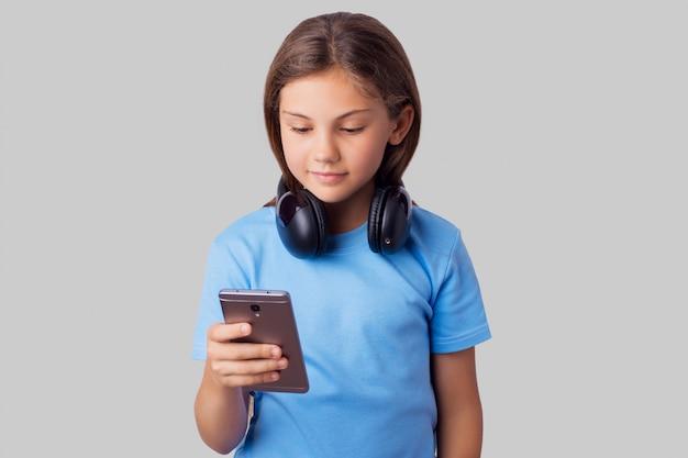 Jovem garota usando fones de ouvido sem fio bluetooth para ouvir música.