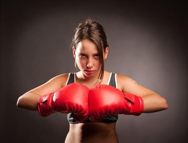 Jovem garota usando luvas de boxe vermelhas