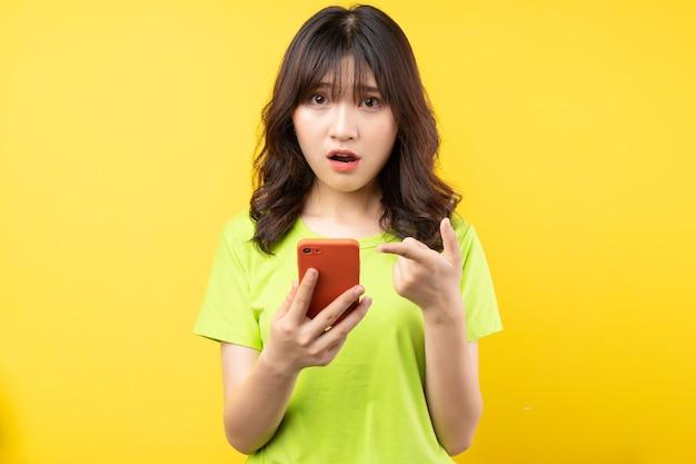 Jovem garota usando o telefone com expressão de surpresa