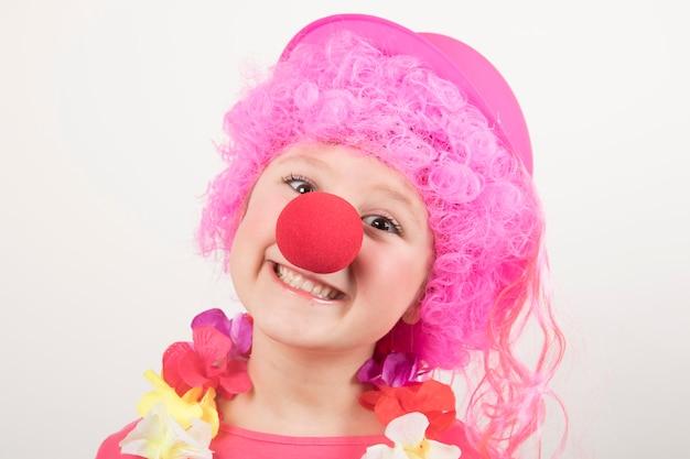 Jovem garota usando óculos de peruca e palhaço e sorrindo para o carnaval
