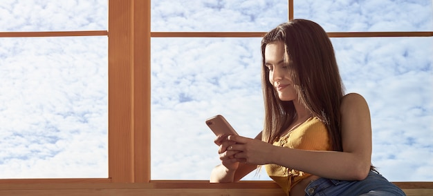 Jovem garota usando smartphone e configuração no peitoril da janela, com espaço de cópia