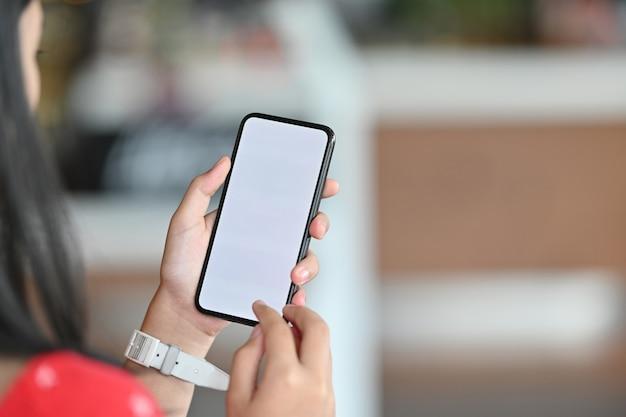 Jovem garota usando telefone celular. telefone inteligente de tela em branco para montagem.