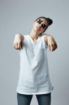 Jovem garota vestida de camiseta branca e jeans com cruzes pretas de fita adesiva nos olhos fica no fundo branco no estúdio como um zumbi.
