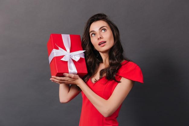 Jovem garota vestida de vermelho está sacudindo a caixa com o presente de aniversário. retrato de mulher encaracolada de olhos azuis em fundo preto.