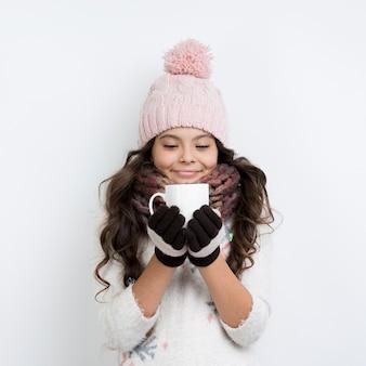 Jovem garota vestindo roupas de inverno e bebendo chá