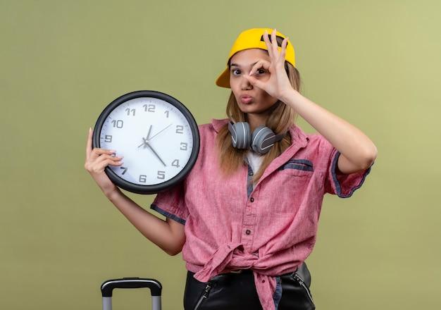 Jovem garota vestindo uma camisa rosa com boné e fones de ouvido no pescoço segurando um relógio de parede fazendo ik cantar olhando através desta placa