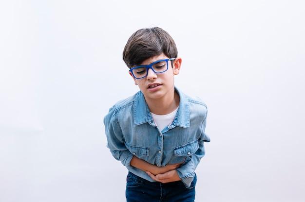 Jovem garotinho com camisa elegante em pé com fundo isolado com a mão na barriga porque náusea, doença dolorosa, mal-estar. conceito de dor.