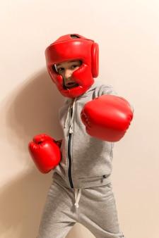 Jovem garoto boxeador com luvas de boxe vermelhas chutando foto de esporte
