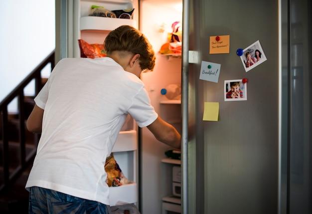 Jovem garoto caucasiano abrir a geladeira à procura de algo para comer