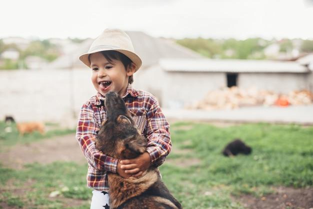 Jovem garoto caucasiano com chapéu na cabeça brincando do lado de fora com seu cachorro abraçando-o