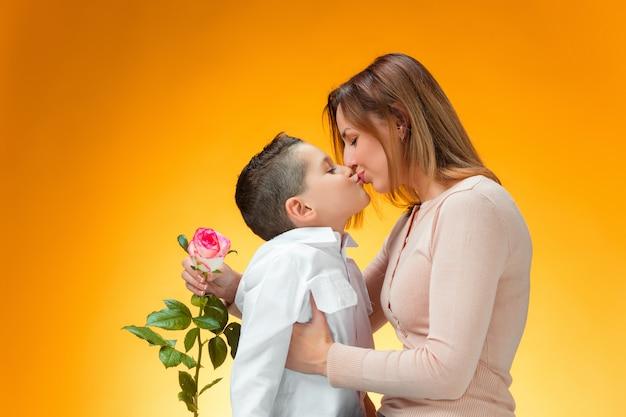 Jovem garoto dando rosa vermelha para sua mãe