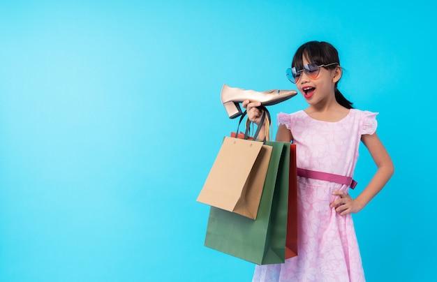 Jovem garoto de garota da ásia segurando o sapato com sacola de compras